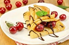 Блинчики с сиропом вишни и шоколада на доске Стоковое Изображение RF