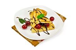 Блинчики с сиропом вишни и шоколада на салфетке Стоковая Фотография