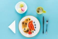 Блинчики с ягодами на плите с macarons на голубой предпосылке Стоковое Изображение