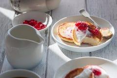 Блинчики творога лета на белых плитах на деревянном столе с кофе, молоком, сметаной и вареньем, крупным планом Стоковая Фотография