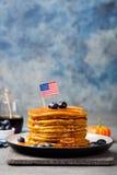 Блинчики тыквы с сиропом и голубиками клена на плите с американским флагом на верхней части Стоковое Изображение RF