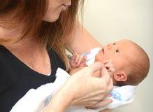 Бдительный newborn смотреть вверх на маме стоковое изображение