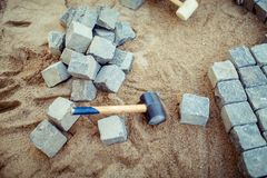 Блоки мостоваой, на песке, с инструментами и деталями конструкции Класть булыжник мостоваой для открытой террасы стоковые фотографии rf