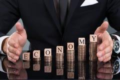 Блоки экономики бизнесмена защищая на штабелированных монетках Стоковая Фотография RF