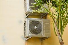 Блоки Airconditiong на желтой стене с зеленым заводом десерта Стоковое фото RF