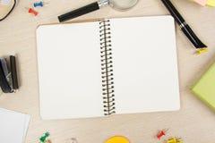 Блокнот белого пробела открытый Стол таблицы офиса с комплектом красочных поставек, чашкой, ручкой, карандашами, цветком, примеча Стоковое Изображение RF