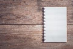 Блокнот/выровнянная бумага на взгляд сверху деревянного стола Стоковая Фотография RF