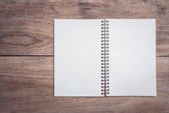 Блокнот/выровнянная бумага на взгляд сверху деревянного стола Стоковое Фото