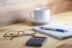Блокнот в коробке с ручкой, калькулятором, и стеклами на чашке чаю деревянного стола на заднем плане Стоковое фото RF