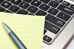 Блокнот и ручка на черной клавиатуре Стоковое Изображение RF