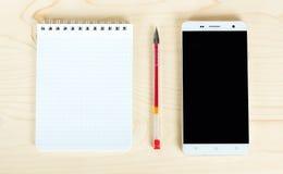 Блокнот и телефон на таблице стоковое изображение