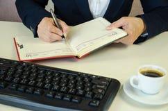 Блокнот, ручка, клавиатура, caffee и руки Стоковое Фото