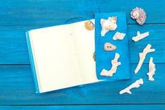Блокнот с раковинами на голубых досках, copyspace Стоковое Фото