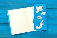 Блокнот с раковинами на голубых досках, copyspace Стоковая Фотография