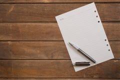 Блокнот с ручкой на деревянном столе офиса стоковое изображение rf