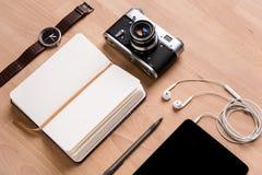 Блокнот, таблетка, наушники, вахта камеры и ручка на деревянном столе Стоковое Изображение RF