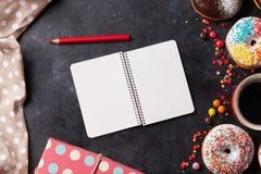 Блокнот, donuts и кофе на каменной таблице Стоковые Изображения RF