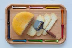 Блок вкусного сыра на разделочной доске с ножом и тройником гольфа стоковое фото