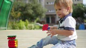 Блок строения мальчика пластичный на деревянном столе в парке видеоматериал