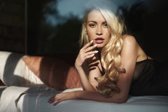 Блондинка в кровати в солнце Стоковое фото RF