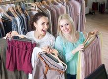 Блондинка и брюнет выбирая новую одежду в магазине моды Стоковая Фотография