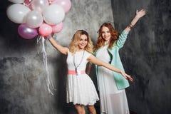Блондинка и redhead 2 молодых очаровательных подруги на партии с воздушными шарами На серой текстурированной предпосылке Стоковое фото RF