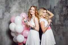 Блондинка и redhead 2 молодых очаровательных подруги на партии с воздушными шарами На серой текстурированной предпосылке Стоковые Фото