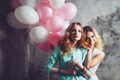 Блондинка и redhead 2 молодых очаровательных подруги на партии Стоковое фото RF