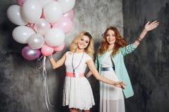 Блондинка и redhead 2 молодых очаровательных подруги на партии Стоковое Фото
