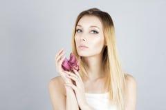 Блондинка красоты с розовым цветком в руке Женщина с перманентностью составляет Сторона красотки Стоковые Фотографии RF