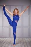 Блондинка спортсмена гимнаста женщины красивая одела в специальном костюме для одежды спорта йоги фитнеса призонной сделанной ней Стоковое фото RF