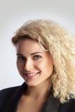 Блондинка с вьющиеся волосы усмехаясь на камере Стоковое фото RF