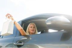 Блондинка с покупками в автомобиле Стоковая Фотография RF