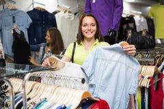 Блузка покупок женщины в магазине одежды Стоковое Изображение