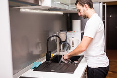 Блюда счастливого молодого человека стоя и моя на кухне Стоковые Изображения
