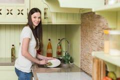 Блюда счастливой молодой женщины моя в кухне стоковые изображения rf