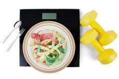Блюда с масштабами и гантели на белой предпосылке Стоковые Изображения