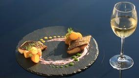Блюдо изысканной кухни Конец-вверх Рыбы с молодыми картошками mullet С стеклом белого вина Ресторан Primorsik видеоматериал