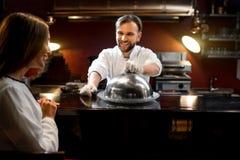Блюдо сервировки кашевара шеф-повара к клиенту Стоковое Изображение