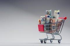 Вагонетка покупок вполне денег евро - банкнот - валюта Символический пример тратить деньги в магазинах, или выгодное приобретение Стоковое Изображение RF