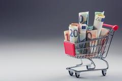 Вагонетка покупок вполне денег евро - банкнот - валюта Символический пример тратить деньги в магазинах, или выгодное приобретение Стоковое Изображение