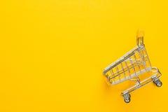 Вагонетка покупок на желтой предпосылке Стоковые Фотографии RF