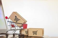 Вагонетка с коробками на ноутбуке Онлайн покупки, электронная коммерция и всемирная грузя концепция стоковое фото rf
