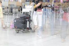 Вагонетка с чемоданами, неопознанная женщина идя в авиапорт, станция багажа авиапорта человека, Франция Движение нерезкости, двой Стоковые Изображения