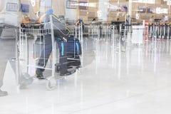 Вагонетка с чемоданами, неопознанная женщина идя в авиапорт, станция багажа авиапорта человека, Франция Движение нерезкости, двой Стоковая Фотография RF
