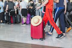 Вагонетка с чемоданами, неопознанная женщина идя в авиапорт, станция багажа авиапорта человека, Франция Стоковое Изображение
