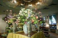 Вазы металла в форме кубка с букетами цветков на таблице Стоковое Изображение RF