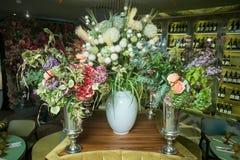 Вазы металла в форме кубка с букетами цветков на таблице Стоковая Фотография