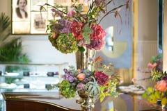 Вазы металла в форме кубка с букетами цветков на таблице Стоковые Изображения