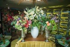 Вазы металла в форме кубка с букетами цветков на таблице Стоковые Фото